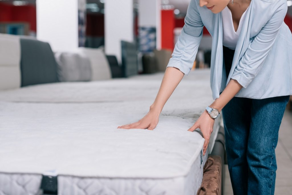 Woman inspecting beds in the store