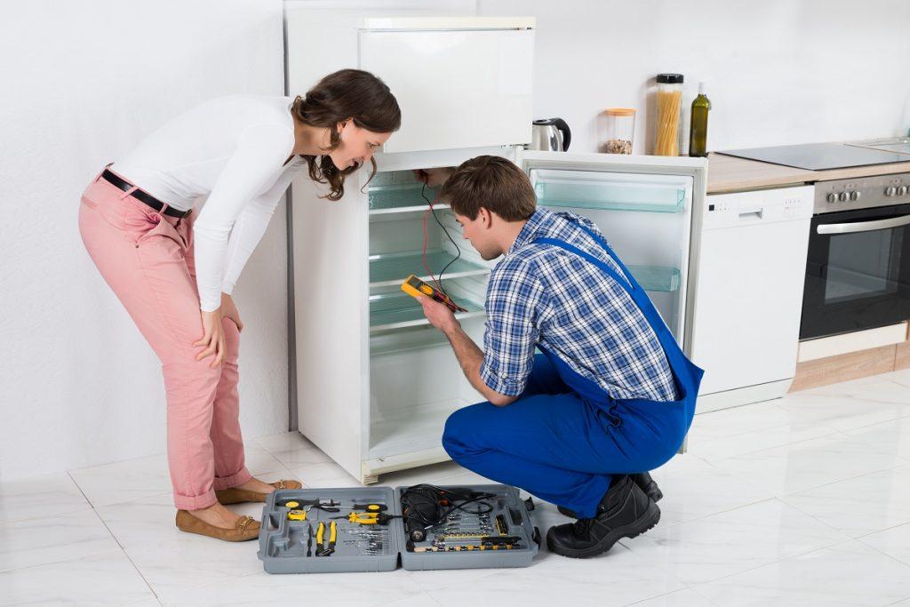 Woman watching man repair fridge