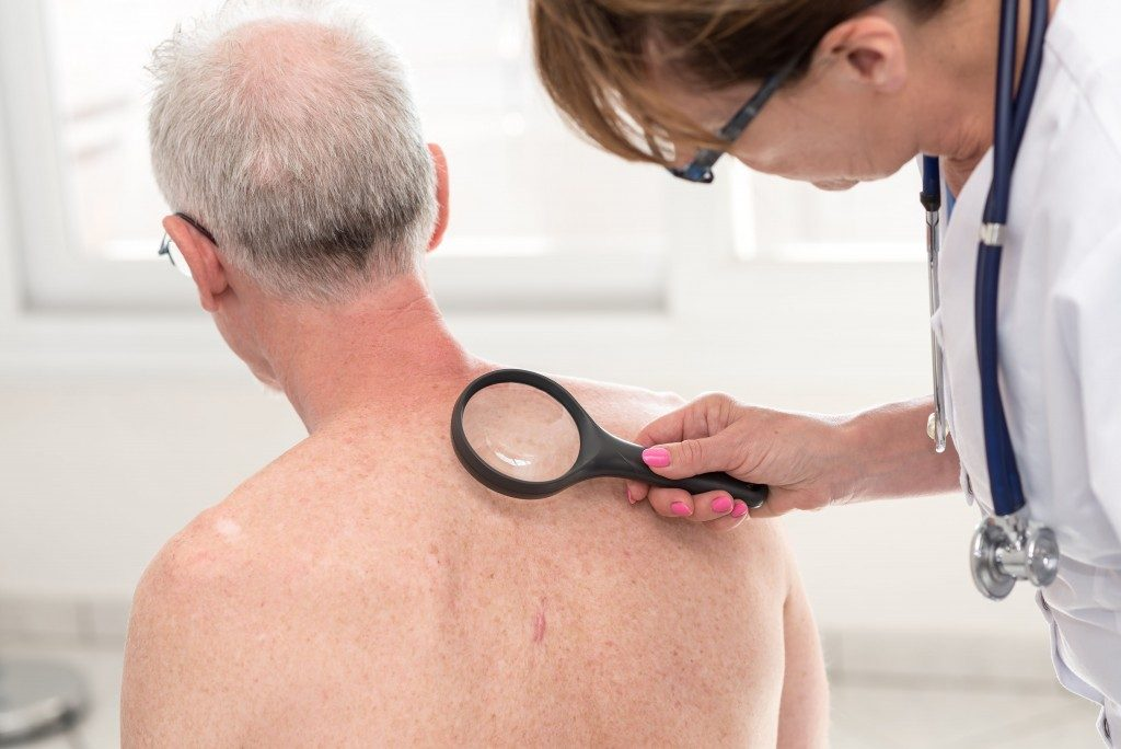 doctor examining back of an old guy