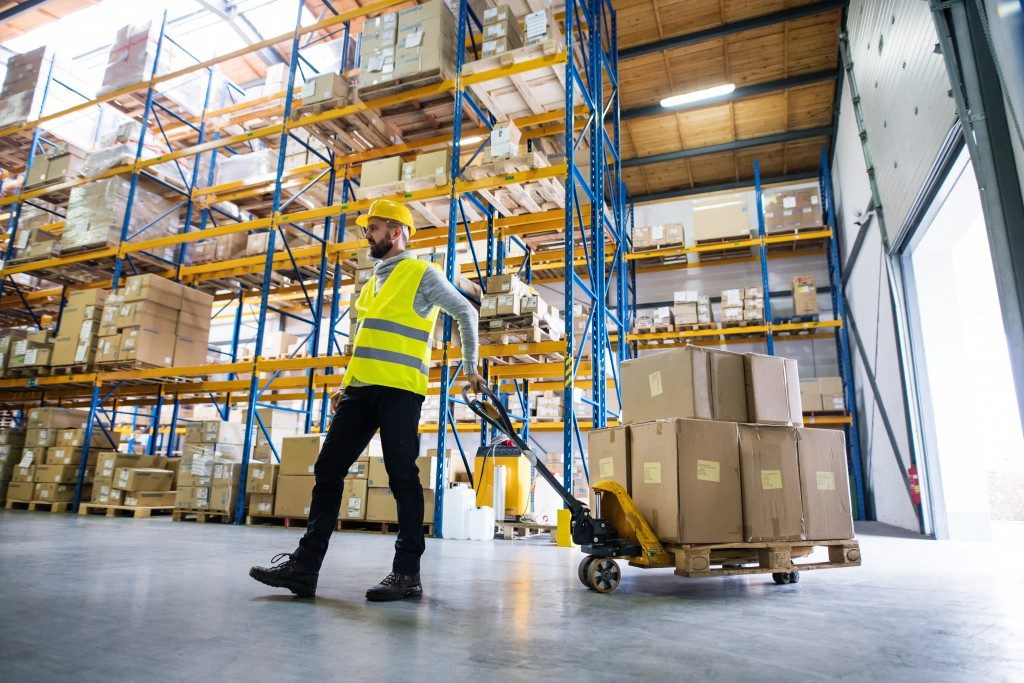 employee wearing safety hat and vest while working inside the warehouse