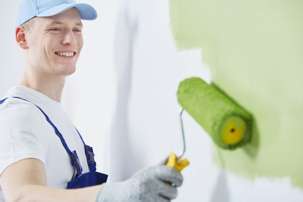 Man painting the wall with green paint