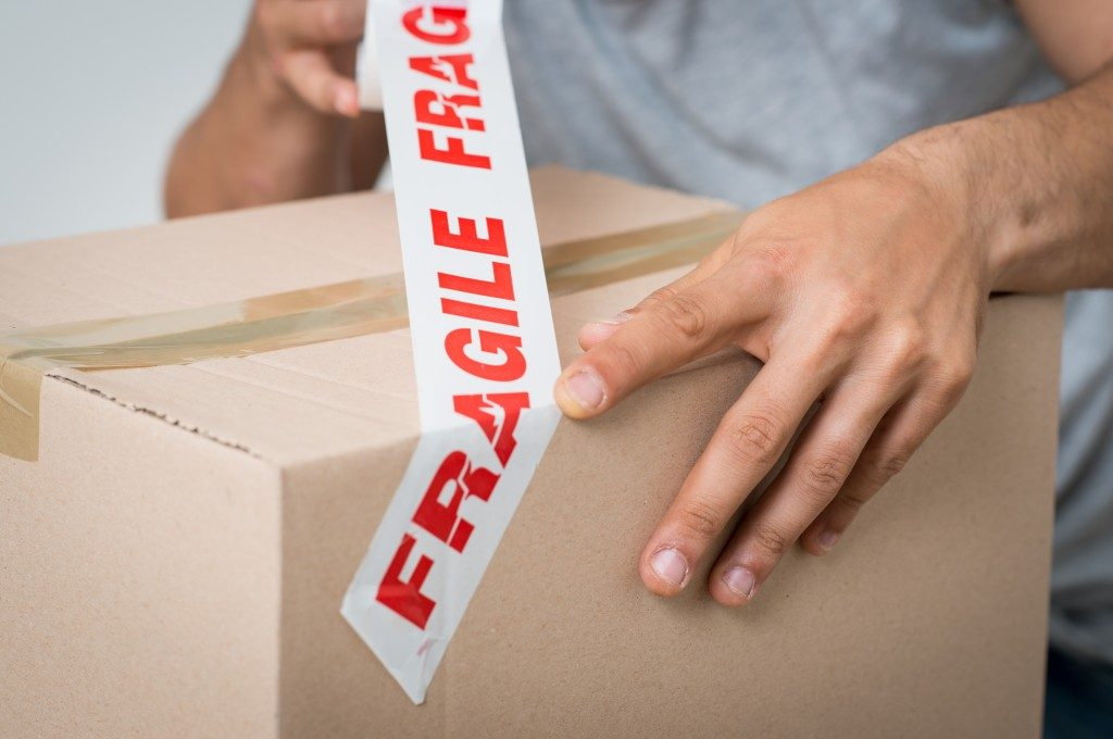 Placing a fragile sticker on a box