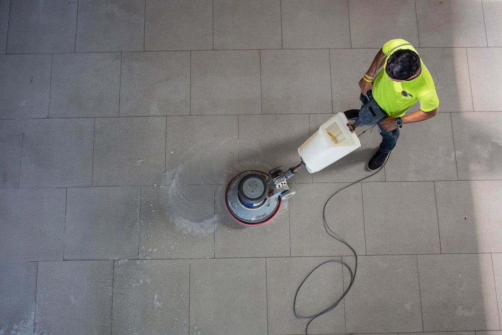 contractor cleaning the floor using a machine