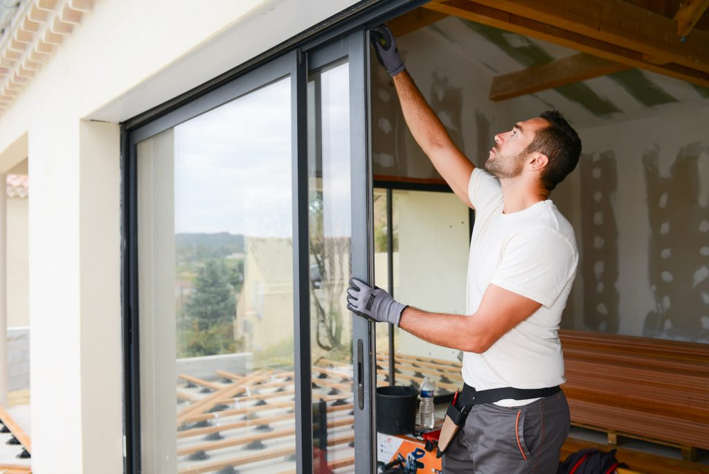 Man fixing glass sliding door