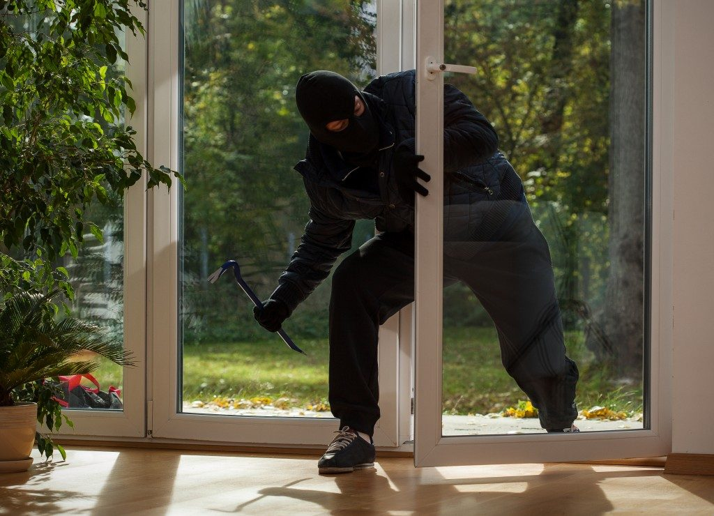 Burglar entering to house trough balcony window