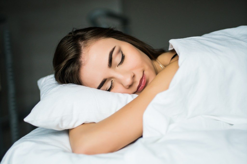 Female sleeping while hugging her pillow