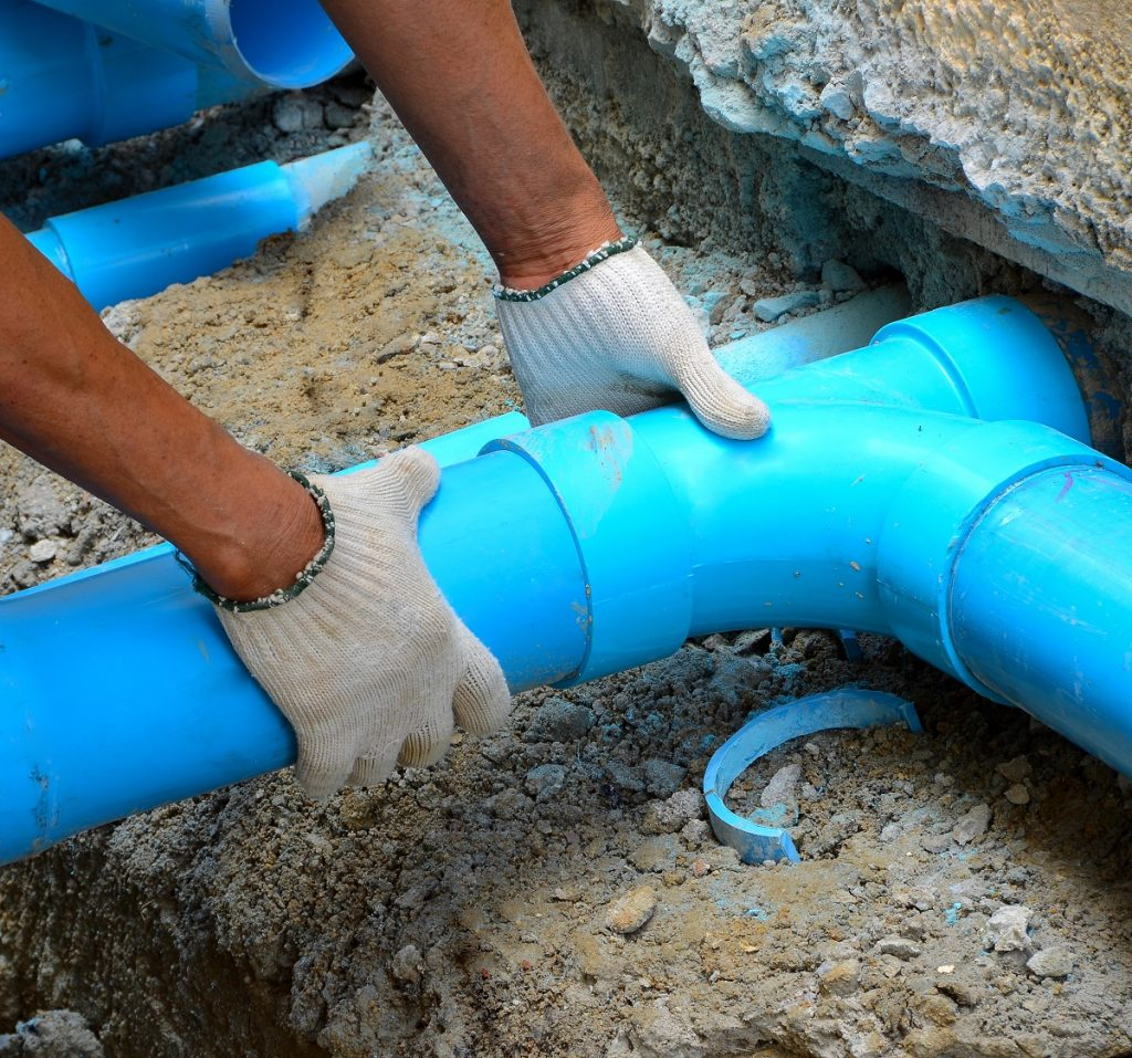 man fixing drainage system