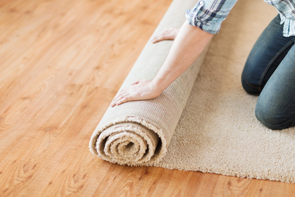 man rolling a carpet on the floor