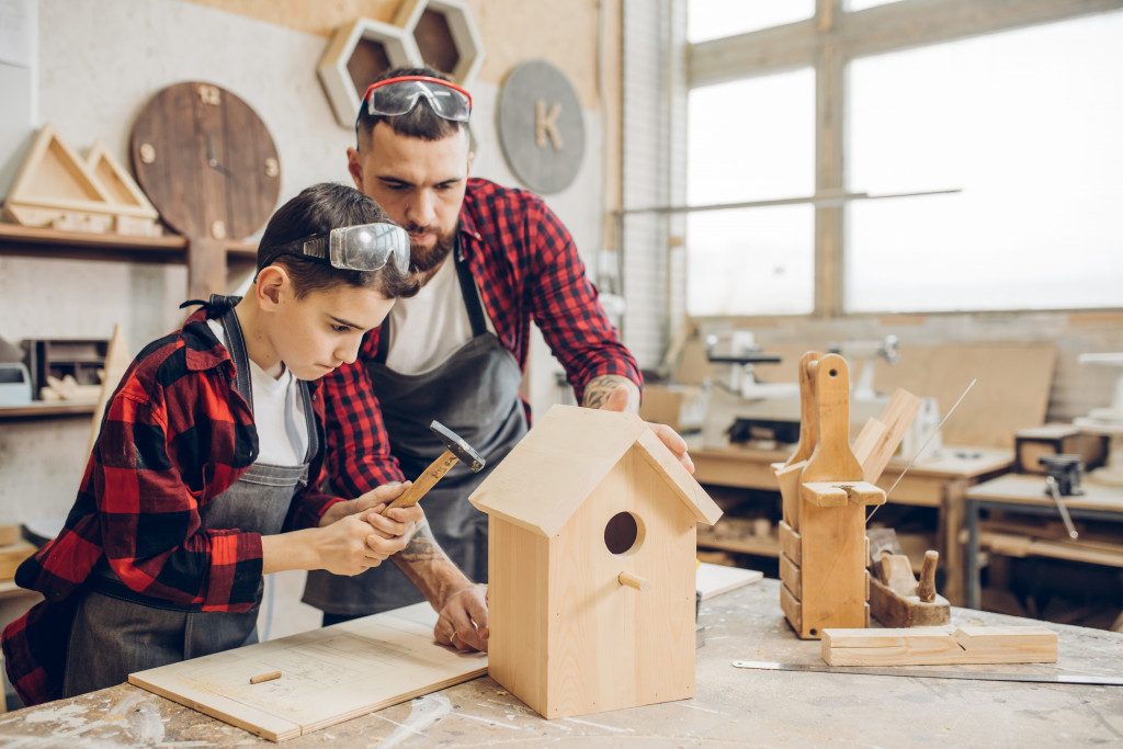 father and son building a bird house