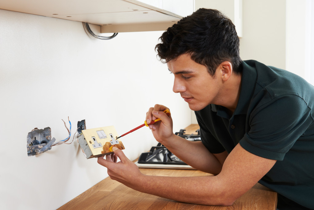 man fixing an outlet
